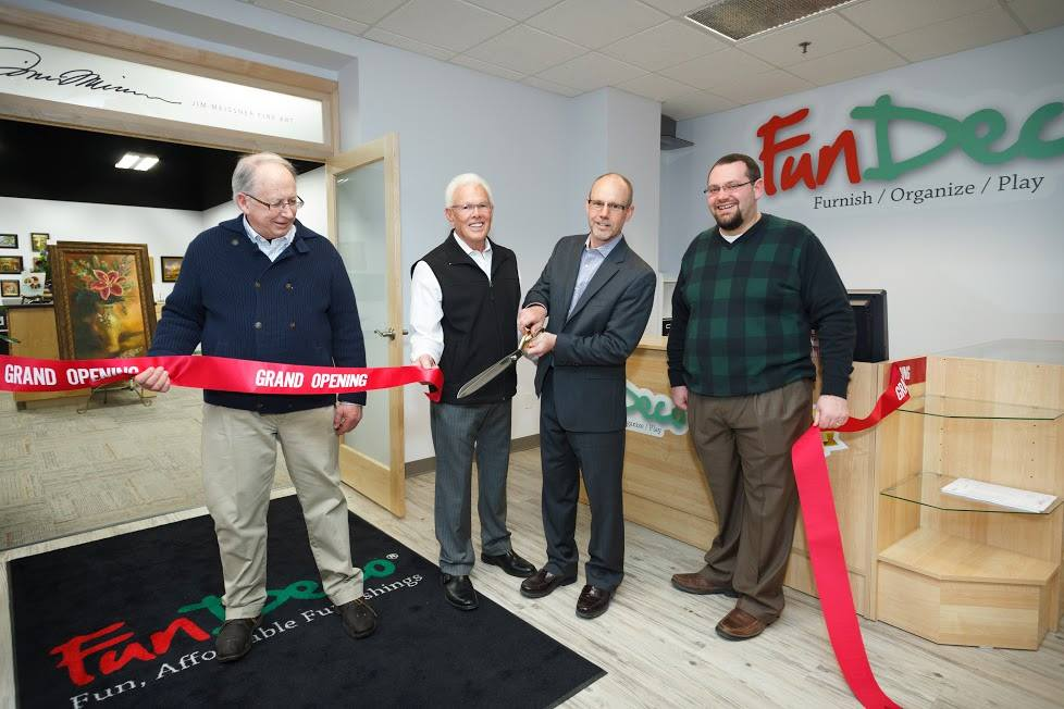 FunDeco Owners clipping Grand Opening ribbon in office