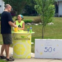 Child serving lemonade from a FunDeco Lemonade Stand